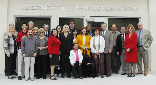 Picture of Chancellor and APTC Staff outside of building.